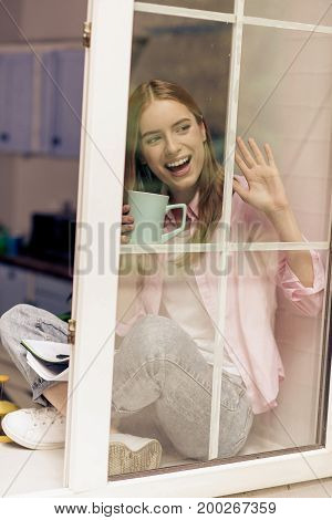 Girl on a windowsill wagging to someone. Young smiling female drinking tea or coffee, sitting close to open window.
