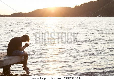 Young man sitting on end of dock with head down