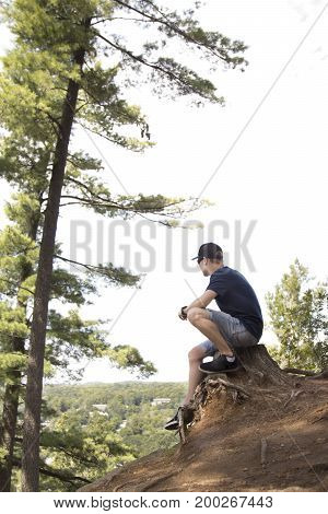 Teenager sitting on old stump and looking down over cliff