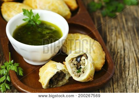 Empanadas with chimichurri sauce on wooden table