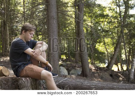 Young man sitting on log and looking down