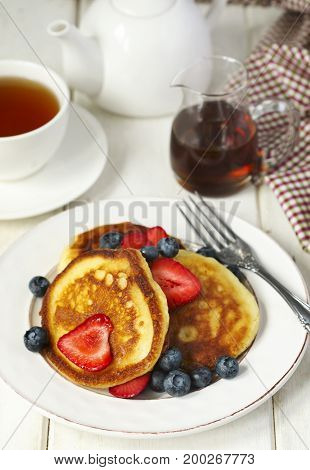 Pancakes with strawberries blueberries and maple syrup for a breakfast.