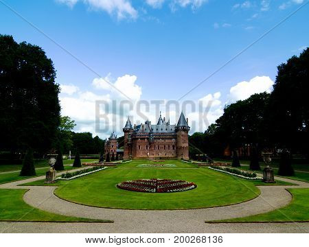 Medieval Castle De Haar from side of Flower Garden Alley against Blue Sky Outdoors. Utrecht Netherlands