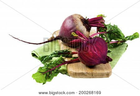 One Full Body Fresh Raw Organic Beet and Half with Green Beet Tops on Wooden Board and Napkin isolated on White background