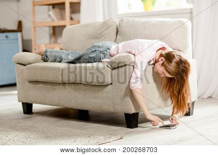 Young girl lying on sofa, typing on smartphone. Female on couch looking on floor, playing with phone.