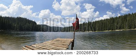 Panorama of alpine lake with pier with life jacket