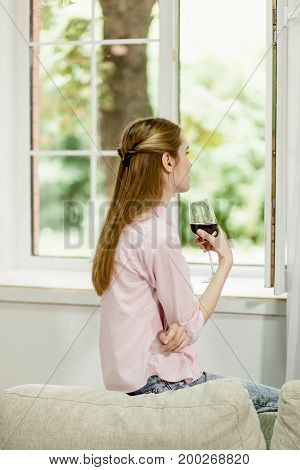 Young girl sitting on sofa, close to open window, holding glass of red wine. Female looking out the window, drinking wine at home.