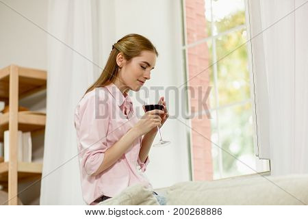 Young female sitting next to window, thinking holding wineglass with both hands. Girl with closed eyes dreaming, drinking red wine.