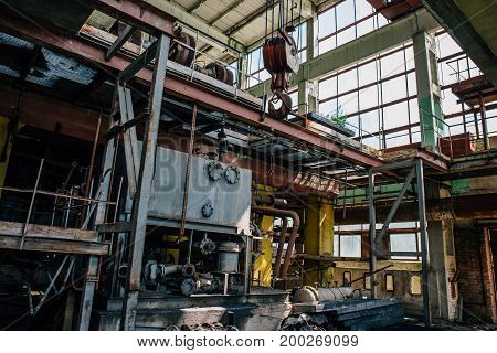 Abandoned factory inside interior with equipment, iron rigs, pipes, toned