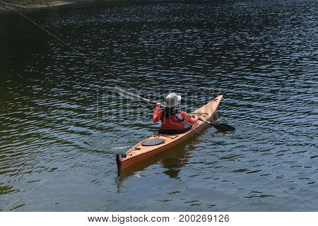 Young woman paddling in mountain lake alone