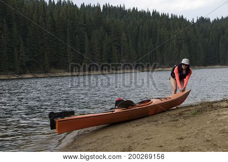 Young woman pulling her kayak on a shore before the rain