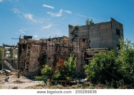 The territory of the abandoned factory, old abandoned buildings, metal structures, post apocalypse concept