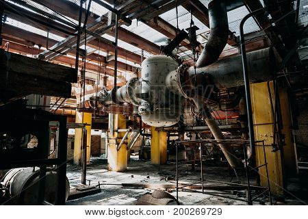 Metal rusty equipment, large industrial pipes in abandoned factory in workshop room, toned