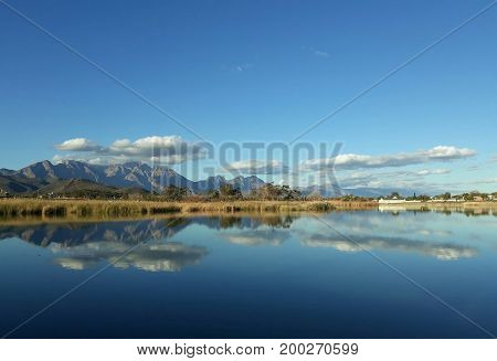 Calm lake waters reflecting clouds and blue sky