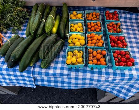 Various varieties of organically grown tomatoes and cucumbers ready for sale.