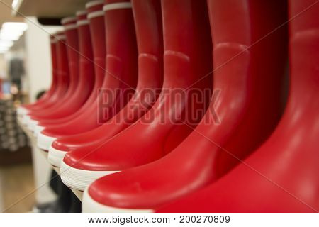 Red rubber boots of different colors on store shelves in a shop