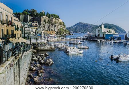 Marina buildings moor of boats and ancient fortress on island of lipari italy