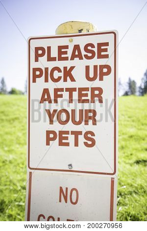 A sign asking people to please pick up after their pets