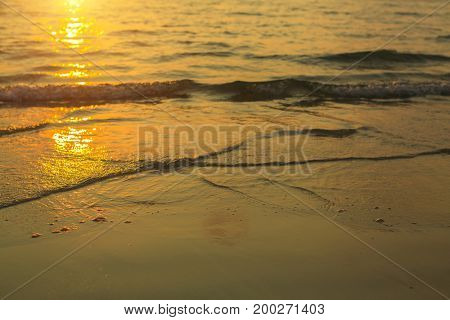 Soft wave of the sea surf in the rays of the setting sun.