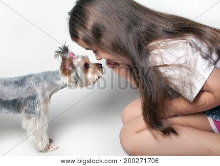A girl with a dog nose to nose on a white background.