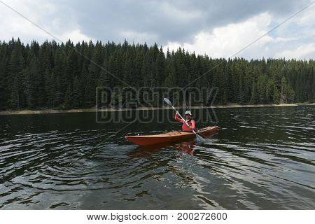 Woman paddling with her sit-in kayak in mountain lake