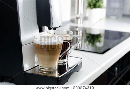 Two cups of coffee home professional coffee machine. coffee machine latte macchiato cappuccino espresso milk foam concept