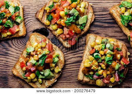 Mexican Latin American style open sandwiches. Vegetarian toasts with maize, avocado, tomatoes on wooden board. Rustic wooden blue background. Top view.