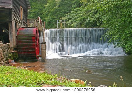 a worn red wheel of a gristmill beside an overflowing dam