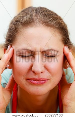 Woman suffering from headache migraine pain. Stressed female.