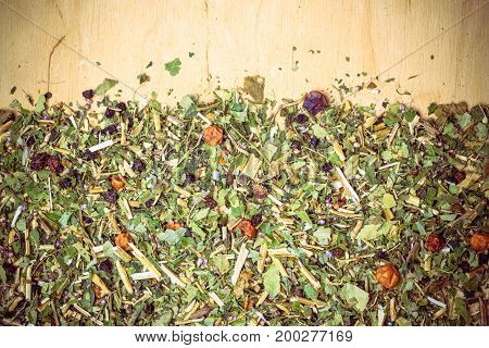 Border frame of assorted natural medical dried herb leaves and fruits on wooden board with copy space