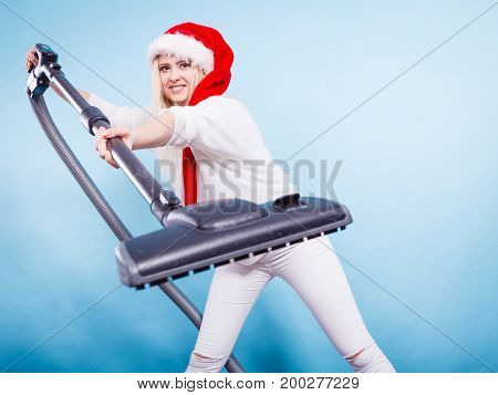 Woman vacuuming the house Teen girl in santa helper hat with vacuum cleaner funny face expression. Christmas time last minute housework concept.