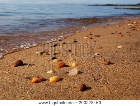 Wet beach pebbles on top of the sand sparkle in the sunlight at the water's edge with gentle bubbling tides rolling in.