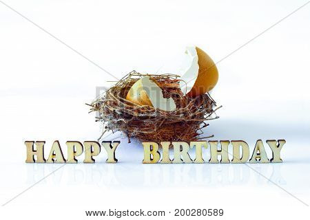 Isolated Broken Eggshell On A Nest With Wood Alphabets For Happy Birthday Concept