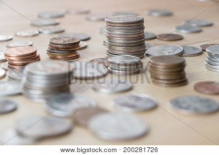 Various American coins in small stacks on wooden surface