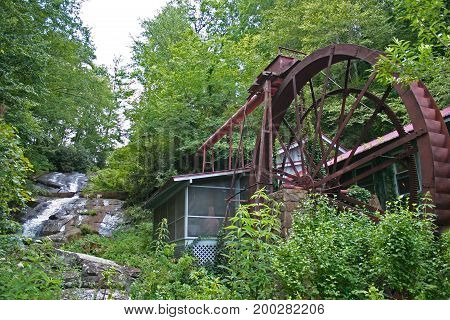 a small stream turns a large metal wheel to power a gristmill