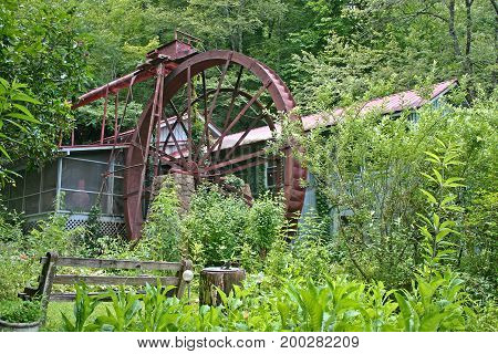 a large metal wheel powers a gristmill