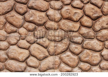 Artificial brown round stones facing on the porch of the building