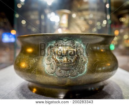 Shanghai, China - Nov 6, 2016: Inside Shanghai Pudong International Airport. A weathered Chinese bronze urn with lionhead relief motif on public display as part of a cultural showcase.