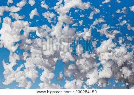 White foam against the blue sky as background .