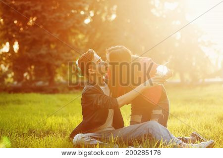 A loving couple of teenagers. Sudden picnic in the park at sunset. Teenagers keep refreshing drinks while sitting on the lawn. They are kissing.