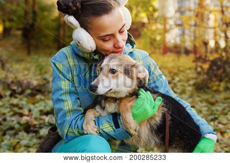 A girl is walking with a mongrel dog. Mistress and home pet for a walk in the autumn park. Caring for animals.