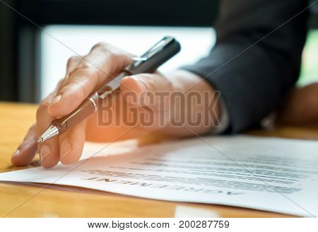 Businessmen holding pens in hand reading documents on the desk,Businessmen holding pens in hand reading contract documents before signing.