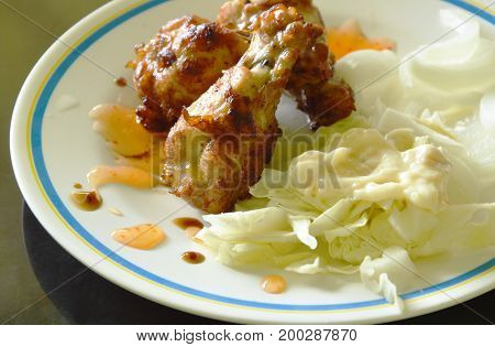 fried chicken wing stick with slice vegetable dressing mayonnaise on dish