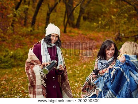 Group of best girlfriends drinking tea after stroll in forest