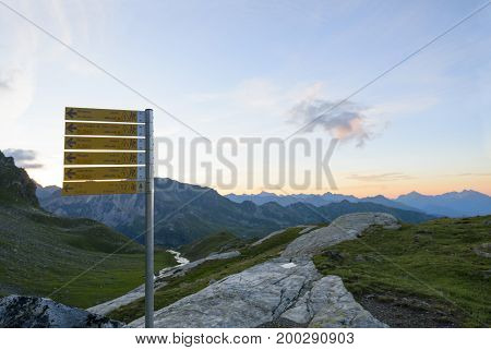 Mountain trail sign with directions hiking time in Italy