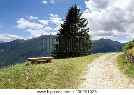 Bench and a curved country road in a mountain landscape