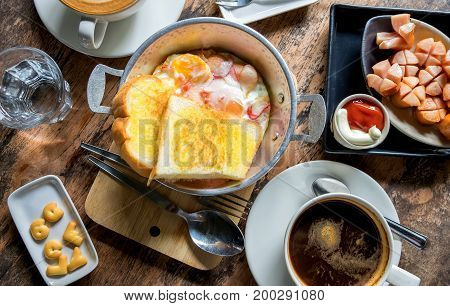 Simple breakfast egg pans baked bread fried sausage and coffee.