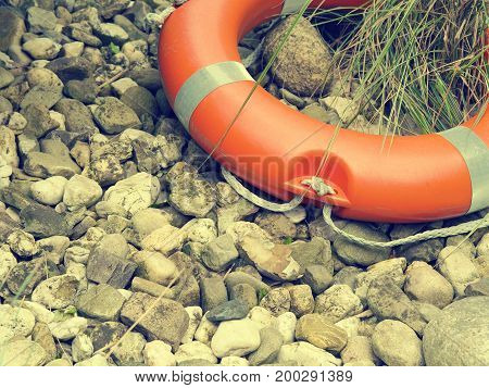 Rescue belt on natural pebbles background with space for text or image