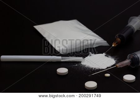 Fake Heroin or diacetylmorphine bag and syringes placed side by side. Low key addictive substance on darkness background.