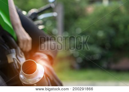 Closeup exhaust and shoe boot touching brake woman biker with glove safety ride acceleration speed control on motorcycle vehicle and nature background.
